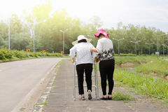 Daughter take care elderly woman walking on street. Daughter take care elderly women walking on street in strong sunlight Stock Image