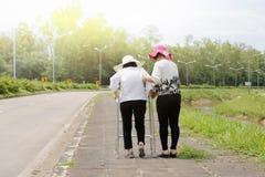 Daughter take care elderly woman walking on street Stock Image