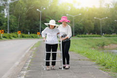 Daughter take care elderly woman walking on street. Daughter take care elderly women walking on street in strong sunlight Stock Photography
