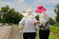 Daughter take care elderly woman walking on street. Daughter take care elderly women walking on street in strong sunlight Stock Photo