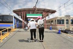 Daughter take care elderly woman on railway station Stock Photos