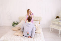 Daughter takes offense at father, and man wants to give child fl. RBaby and dad sit on bed, Dad wants to give daughter flower and girl offended. Young happy Royalty Free Stock Images