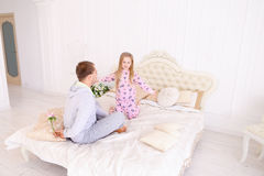 Daughter takes offense at father, and man wants to give child fl. RBaby and dad sit on bed, Dad wants to give daughter flower and girl offended. Young happy Stock Photos