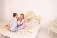 Daughter takes offense at father, and man wants to give child fl. RBaby and dad sit on bed, Dad wants to give daughter flower and girl offended. Young happy Stock Image