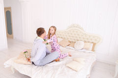 Daughter takes offense at father, and man wants to give child fl. RBaby and dad sit on bed, Dad wants to give daughter flower and girl offended. Young happy Royalty Free Stock Photos