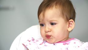 Daughter takes spoon from mom. Mom feeds a small child with a spoonful of vegetables for lunch. Daughter takes spoon from mom. Little baby girl chews vegetables