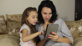 Daughter teaches mother to play the game on the tablet. stock footage