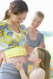 Daughter touching mother?s pregnant stomach as grandmother watches Royalty Free Stock Image