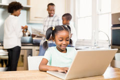 Daughter using laptop in the kitchen. Daughter using laptop against parents in the kitchen royalty free stock photo