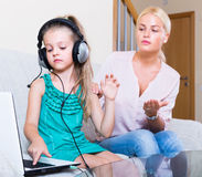 Daughter using laptop instead of studying. Terrified mother watching daughter using laptop instead of studying indoors Royalty Free Stock Images