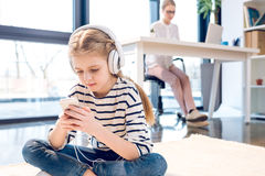 Daughter using smartphone and headphones, businesswoman working behind in office Royalty Free Stock Images