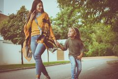 Daughter walking street holding hands her Mother. On the move Stock Image