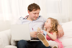 Daughter wants to play with busy dad Stock Image
