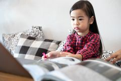 Daughter is watching and playing notebook stock photos