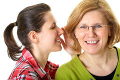 Daughter whisper to her mom, secrecy concept. Daughter whisper something to her mother, secrecy or privacy concept, isolated on white background Stock Photos