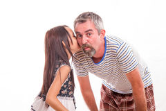 Daughter whispering secret in dad's ear Royalty Free Stock Photos