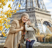 Daughter whispering something to mother near Eiffel tower Royalty Free Stock Photography
