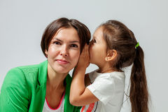 Daughter whispering to mother's ear Stock Photo