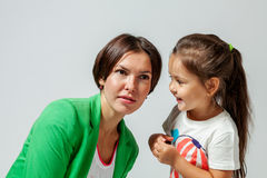 Daughter whispering to mother's ear Royalty Free Stock Photos