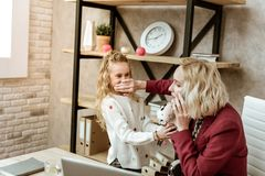 Irritated blonde businesswoman shutting mouth of her daughter. Daughter yelling nearby. Irritated blonde businesswoman shutting mouth of her daughter while she royalty free stock photography