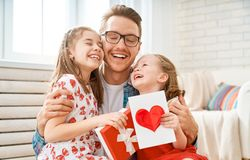 Daughters congratulating dad. Happy father`s day! Children daughters congratulating dad and giving him gift box. Daddy and girls smiling and hugging. Family stock photography