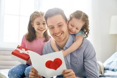 Daughters congratulating dad. Happy father`s day! Children daughters congratulating dad and giving him gift box. Daddy and girls smiling and hugging. Family royalty free stock image