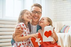 Daughters congratulating dad. Happy father`s day! Children daughters congratulating dad and giving him gift box. Daddy and girls smiling and hugging. Family royalty free stock photo