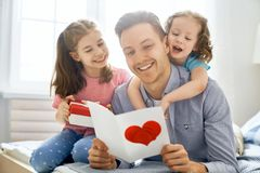Daughters congratulating dad. Happy father`s day! Children daughters congratulating dad and giving him gift box. Daddy and girls smiling and hugging. Family royalty free stock photos