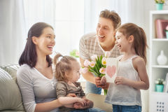 Daughters with dad congratulate mom Stock Photography