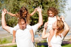 Daughters enjoying their ride on parents shoulders Stock Photography