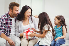 Daughters giving gift to surprised parents Stock Photo