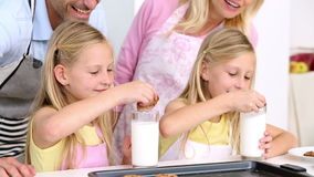 Daughters having cookies and milk with their parents Stock Image