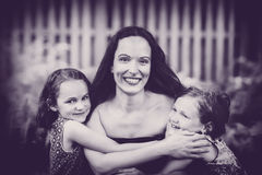 Daughters Hugging their Mother - Black and White Stock Photo