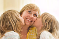 Daughters kissing his mom Royalty Free Stock Photos