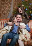 Daughters kissing and hugging dad at christmas eve Stock Image