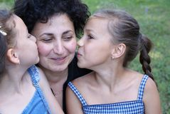 Daughters kissing mother. Preteen girls kissing their mother Stock Photos