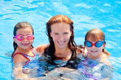 Daughters and mother family swimming in pool. On summer vacation Royalty Free Stock Photo