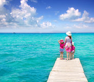 Daughters and mother in jetty on tropical beach Royalty Free Stock Images