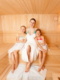 Daughters with mother sitting on bench at sauna Royalty Free Stock Images