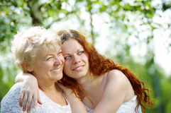 Daughters - mothers. The daughter and elderly mother in a summer garden Royalty Free Stock Photo