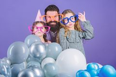 Daughters need father actively interested in life. Birthday party. Father with two daughters having fun. Fatherhood. Concept. Friendly family wear funny party royalty free stock image