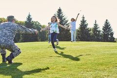 Daughters are running to their soldier father. stock photography
