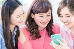 Daughters show mobilephone to mom. Daughters show mom how to use smartphone stock images