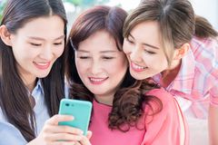 Daughters show mobilephone to mom. Daughters show mom how to use smartphone royalty free stock photography