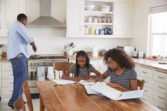 Daughters Sitting At Table Doing Homework As Father Cooks Meal royalty free stock photos