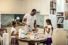 Daughters wearing skirts and white shirts making cupcakes with father stock images