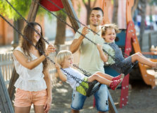 Daughters on swings with parents Royalty Free Stock Photo