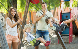 Daughters on swings with parents Stock Photo