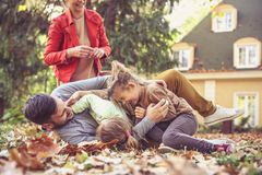 Daughters tickling father , playing with parents. Young family playing in park Stock Photography