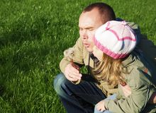 Daugter and father blowing a dandelion stock image